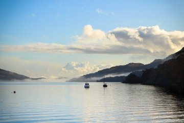 Looking South on the West shore of Loch Lomond, little boats float in front of cloud-covered hills.
