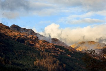 Low clouds are forming around the sunset light covered peaks of the Arrochar Alps