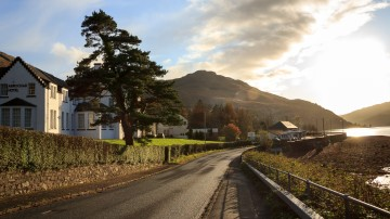 The Arrochar main road, with the Arrochar Hotel on the left, and sunset over Loch Long on the right.